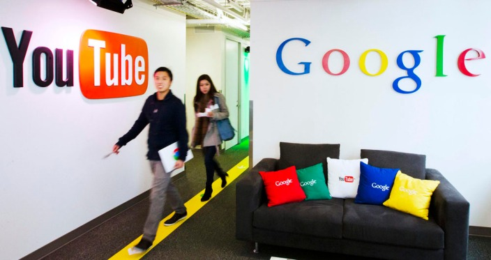 File photo shows people walking by a YouTube sign at the new Google office in Toronto