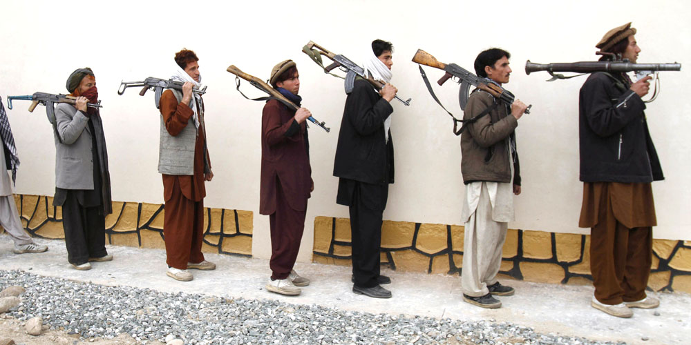FILE - In this Monday, March 12, 2012 file photo, former Taliban militants line up with their weapons to attend in a joining ceremony with the Afghan government in Mehterlam, Laghman province, east of Kabul, Afghanistan. Secret contacts are again reported to be underway for an Afghanistan peace deal, but neither analysts nor the belligerents see hope they will succeed. (AP Photo/Rahmat Gul, File)