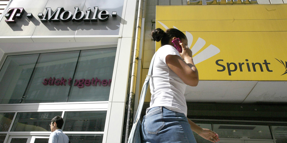A woman talks on her phone as she walks past T-mobile and Sprint wireless stores in New York in this file photo from July 30, 2009. Sprint Corp is mulling a bid for T-Mobile US, according to a report in the Wall Street Journal citing people familiar with the matter. REUTERS/Brendan McDermid/Files (UNITED STATES - Tags: BUSINESS TELECOMS)
