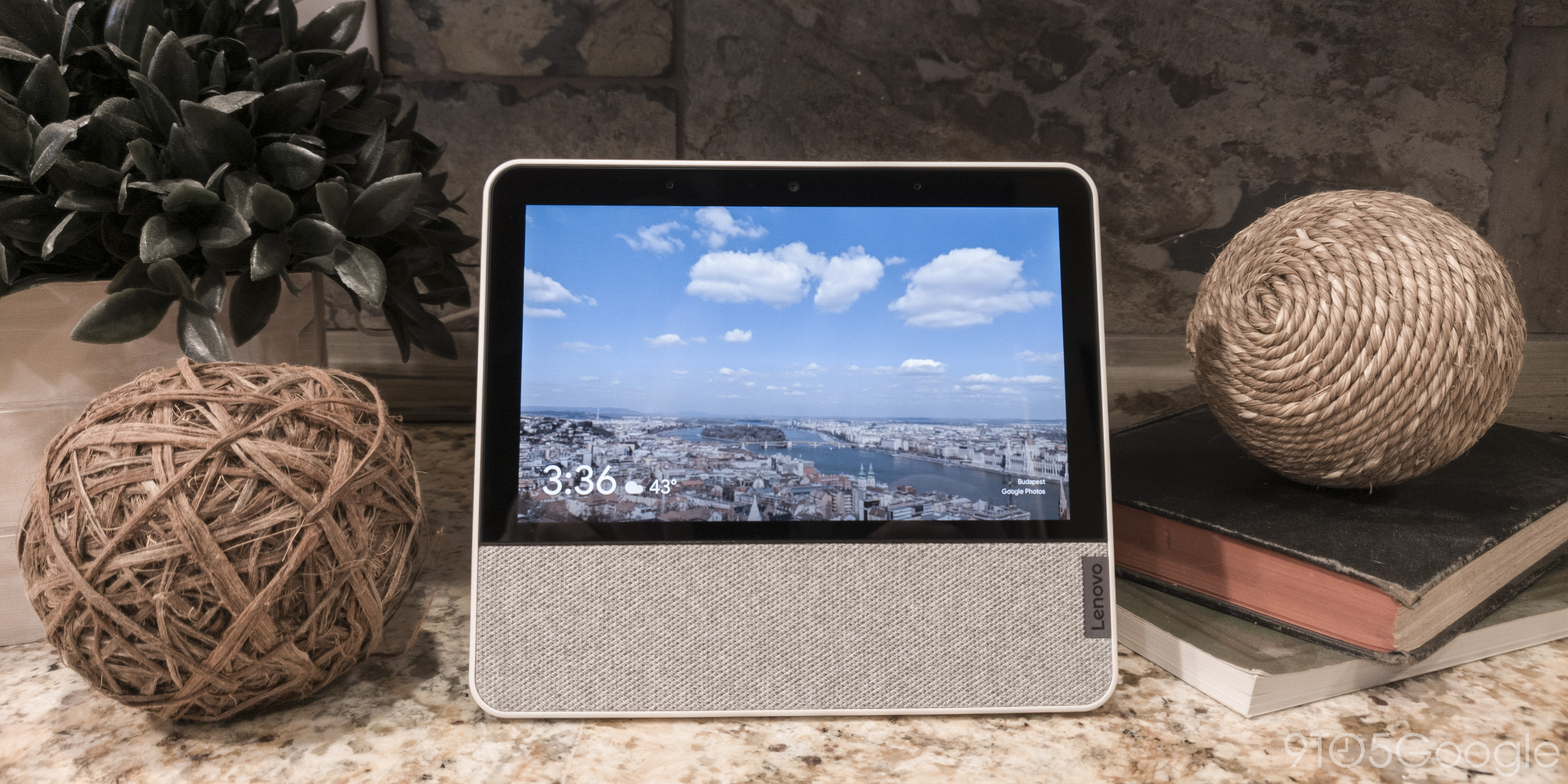 """The Lenovo Smart Display 7"""" sitting on a decorated granite countertop."""